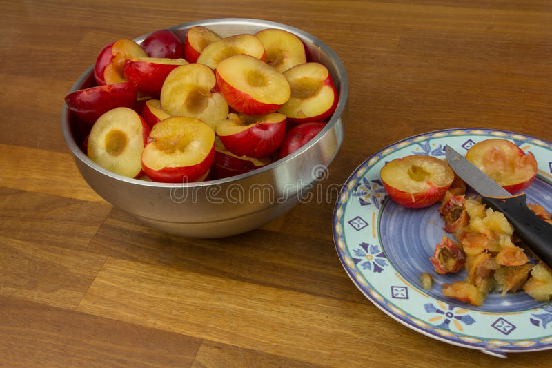 Halfed and stoned plums. Bowl of halfed plums next to a plate with stones royalty free stock photo