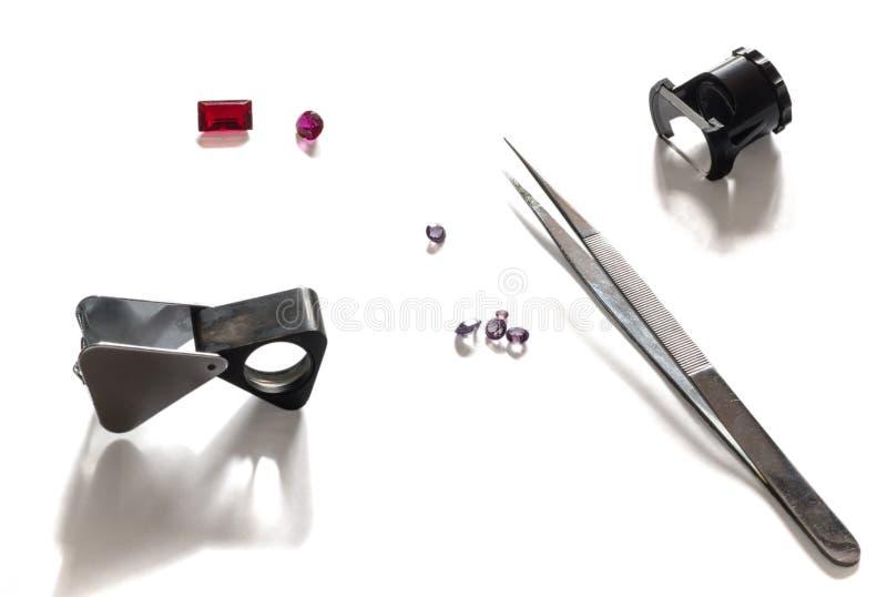 Halfedelsteenevaluatie Hulpmiddelen voor evaluatie die van meer magnifier diamanten, loupe, pincet en gemmen meten die op witte a stock afbeeldingen