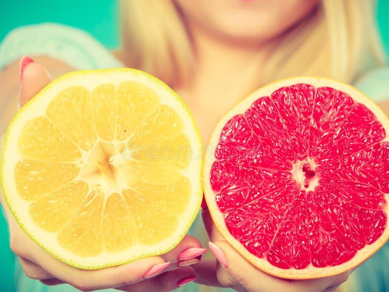 Halfs der gelben roten PampelmusenZitrusfrucht in den menschlichen Händen stockfotos