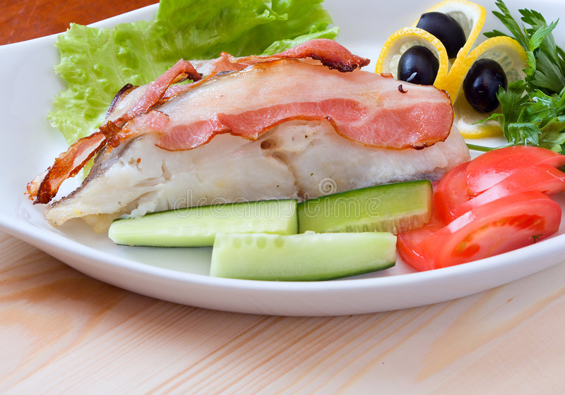 Halibut prepared with vegetables and bacon royalty free stock image