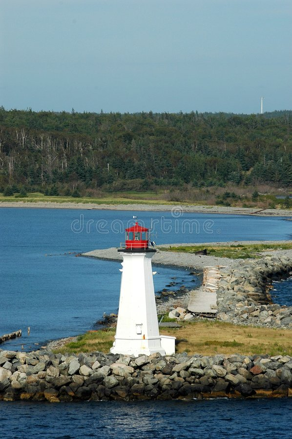 Maugher Beach Lighthouse Nova Scotia. Lighthouse on rocky land spit extending from McNabs Island in Halifax Harbor with treed hill in background with blue sky royalty free stock photography