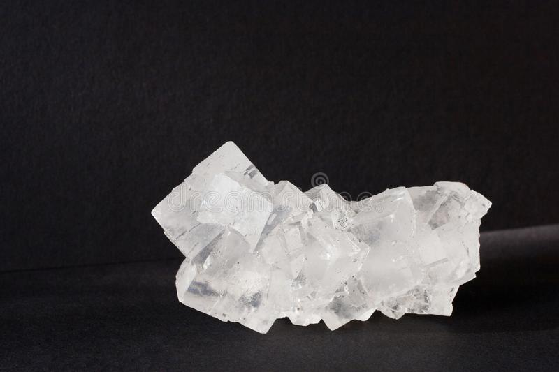 Halite mineral also rock solt on black background. Transparent white cubic halite mineral of sodium chloride crystals also rock salt on black background royalty free stock image