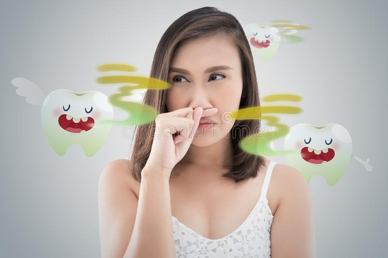 Halitosis or Bad breath. Asian woman in white dress catch her nose because of a bad smell against gray background - Halitosis or Bad breath royalty free stock images