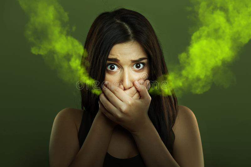 Halitosis concept of woman with bad breath. Halitosis concept of young woman with bad breath covering mouth and looking ashamed stock images