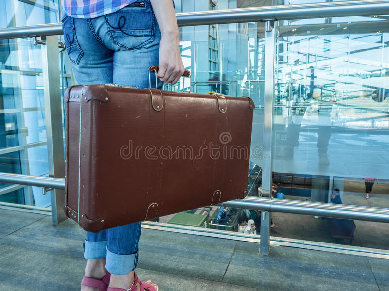 Hall Airport. A woman traveling with retro suitcase stock photography