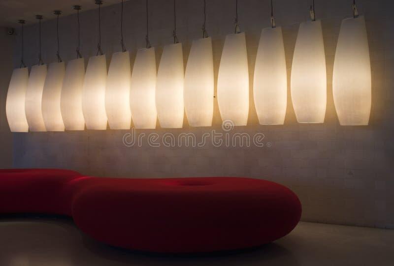 Hall avec le sofa et les lampes rouges photo stock