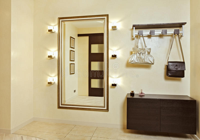 Hall in beige tones with hallstand and golden mirr