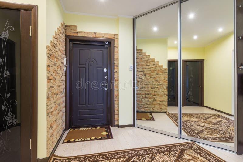 Hall d'entrée spacieux dans l'appartement avec la garde-robe intégrée et les miroirs énormes photos stock