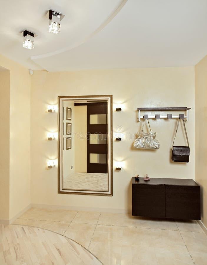 Hall dans des sons beiges avec le hallstand et le miroir photo stock