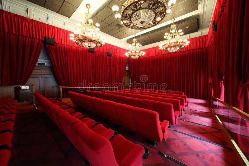 Hall de cinéma avec des lustres et des rangées des sièges photo libre de droits