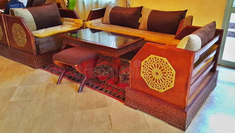 The hall in the hotel of the city of Marrakesh in Morocco with carpet and carved furniture, made in the traditional oriental style royalty free stock photos