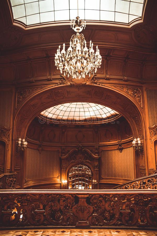 Hall in a mansion with a high domed ceiling. glass window with lattice texture. luxury chandelier. rich baroque interior stock photography