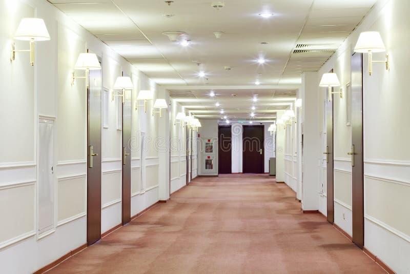 Hall med många dörrar som leder in i hotellrum. arkivfoton