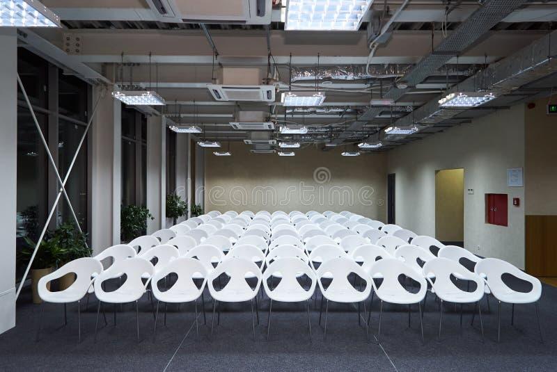 Hall vide d'amphithéâtre avec des rangées des sièges en plastique blancs photo stock