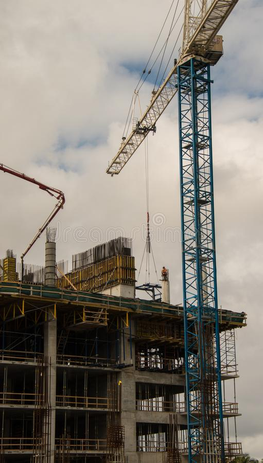 Construction worker on top of concrete pillar with crane royalty free stock photography