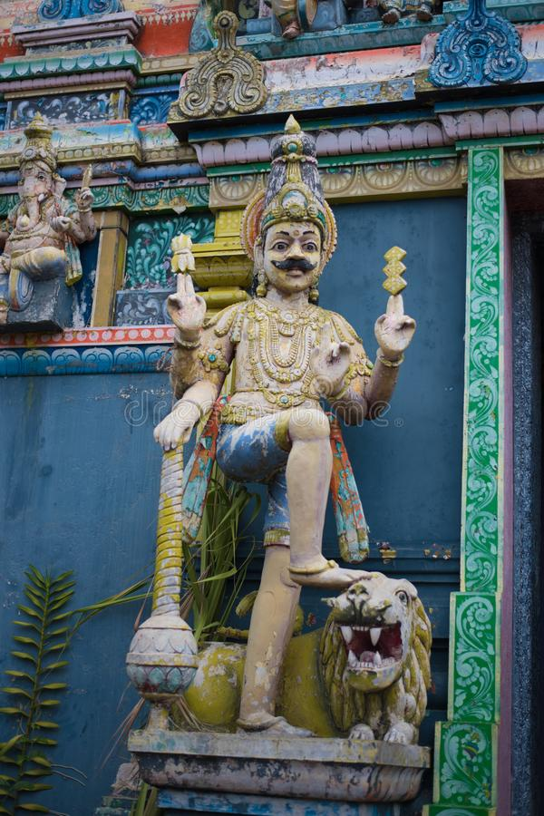 Statue of a saint at the entrance of a buddhist temple in the city stock image
