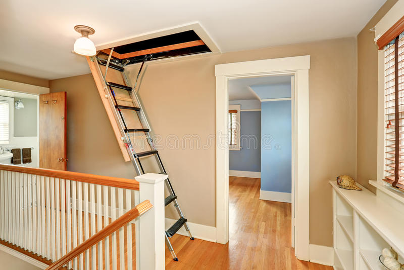 Halleninnenraum mit faltender Dachbodenleiter stockbild