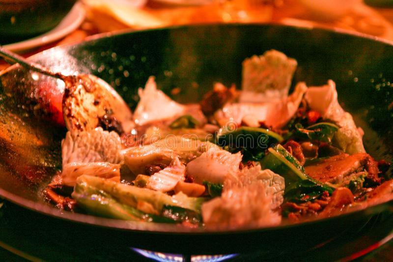 Traditional Chinese dish cooked in a wok pan over an open fire. Beijing, China. royalty free stock photography