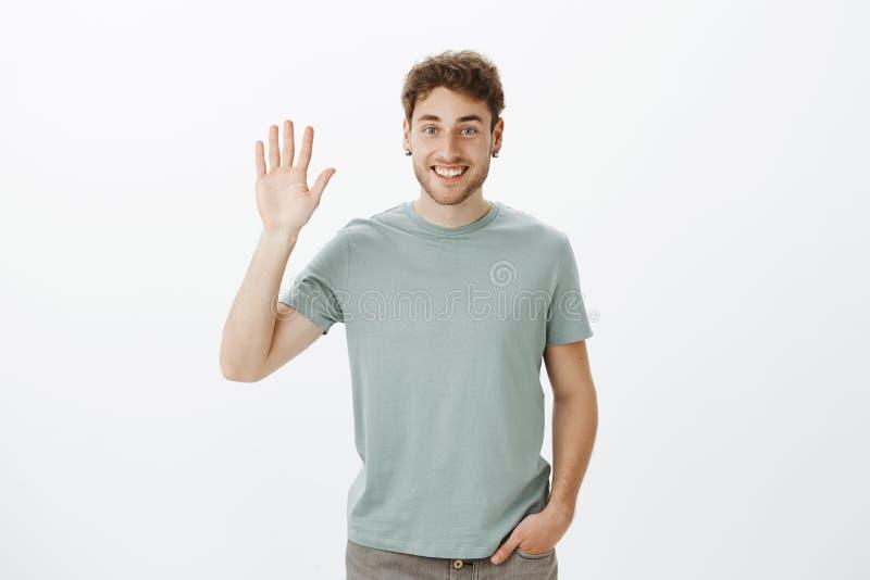 Hallo aardig om u te ontmoeten Portret van knappe uitgaande Europese kerel in toevallige t-shirt die hand opheffen en palm golven stock fotografie