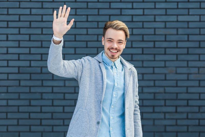 Hallo, aardig om u te zien Portret van de gelukkige knappe jonge blondemens in toevallige stijl die zich met toothy glimlach bevi stock afbeeldingen
