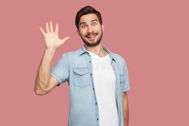 Hallo, aardig om u te zien Portret van de verraste knappe gebaarde jonge mens in blauw stijloverhemd die en zich camera bevinden  stock afbeelding