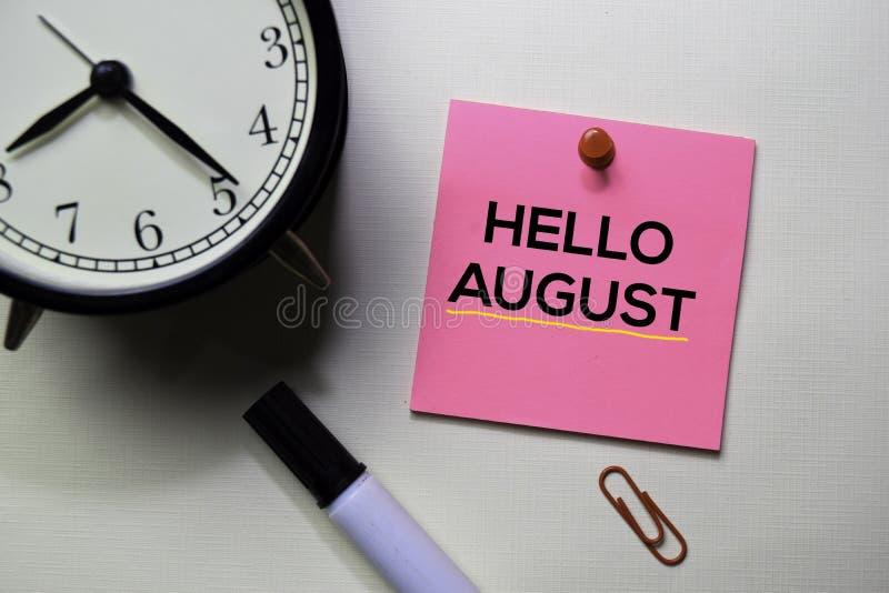 Hallo August-Text auf den klebrigen Anmerkungen lokalisiert auf Schreibtisch lizenzfreie stockfotos
