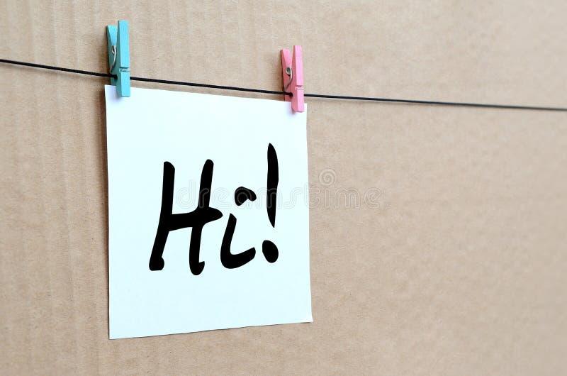 Hallo! De nota wordt geschreven op een witte sticker die met kleren hangt royalty-vrije stock afbeelding