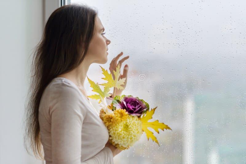 Hallo Herbst Junge lächelnde Frau mit Herbstblumenstrauß von gelben und orange Blumen, von purpurrotem dekorativem Kohl und von A lizenzfreie stockbilder