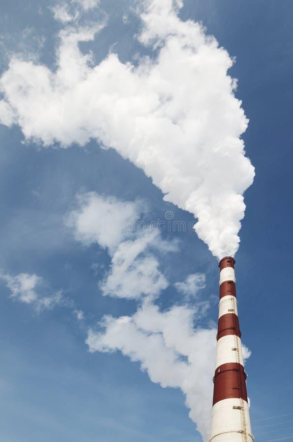 Industriële rook van schoorsteen op blauwe hemel stock afbeeldingen