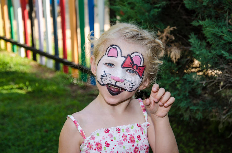 Hallo kitty face painting. Beautiful blond girl with hallo kitty face painting royalty free stock photography