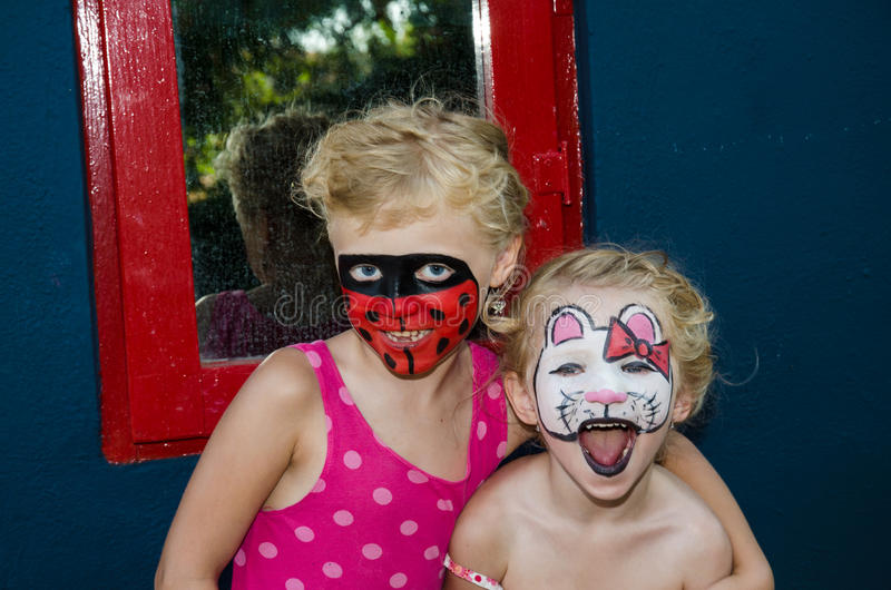 Hallo kitty and ladybug face painting. Beautiful blond girls with hallo kitty and ladybug face painting on floral background stock images