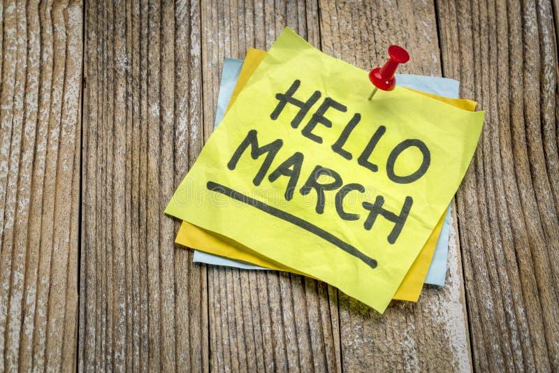 Hallo März-Grüße auf einer klebrigen Anmerkung stockfotos