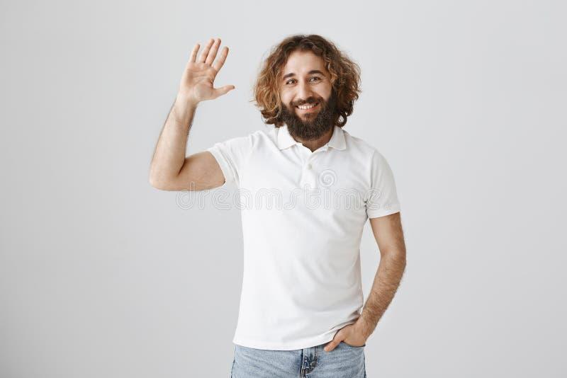Hallo, mijn vriend Portret van knap gewoon oostelijk mannetje met krullend haar en hand opheffen en baard die binnen golven stock afbeelding