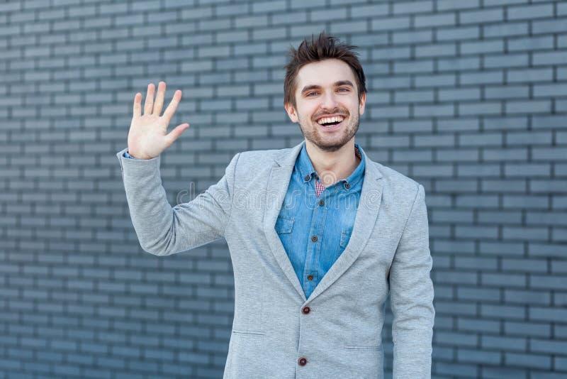 Hallo, nett, Sie zu sehen Porträt des glücklichen hübschen bärtigen Mannes in der zufälligen Art, die Kamera mit Grußgeste steht  lizenzfreie stockfotografie