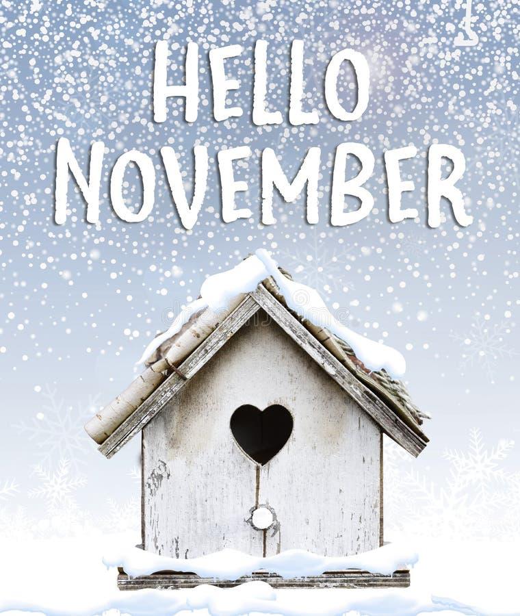 Hallo November-Textwinterschnee, der unten auf netten kleinen Vogel fällt stockfoto