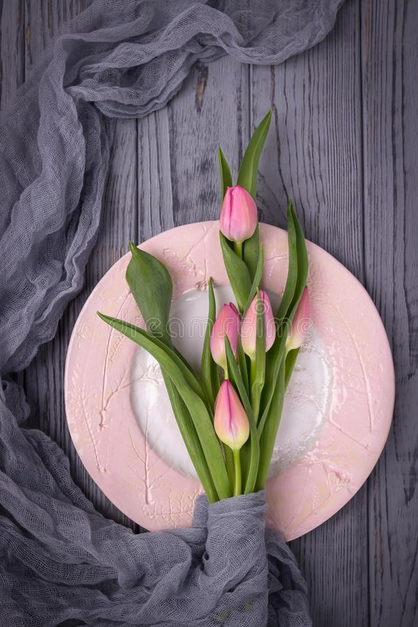 Hallo, spring. Beautiful flowers pink tulips and a pink plate on a gray background. Top view, free space stock photo
