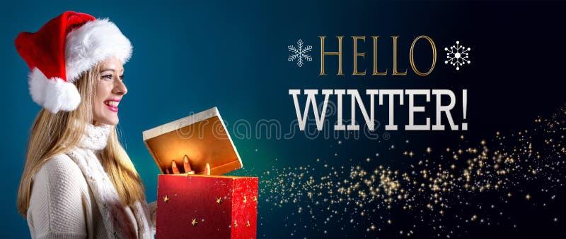 Hallo Wintermitteilung mit der Frau, die eine Geschenkbox öffnet stockbilder