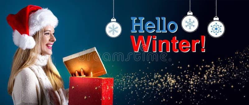 Hallo Wintermitteilung mit der Frau, die eine Geschenkbox öffnet lizenzfreie stockfotos