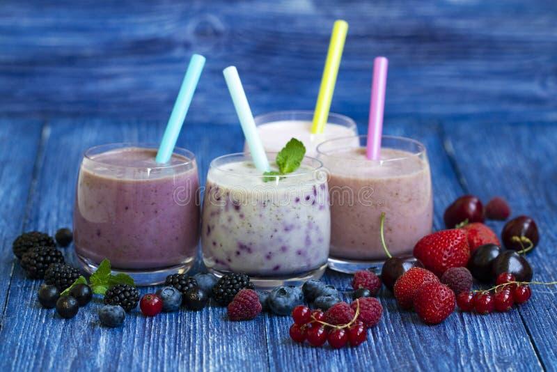 Hallon jordgubbe, björnbär, körsbärsröd smoothie på blå träbakgrund Milkshake med nya bär Sunt royaltyfri foto