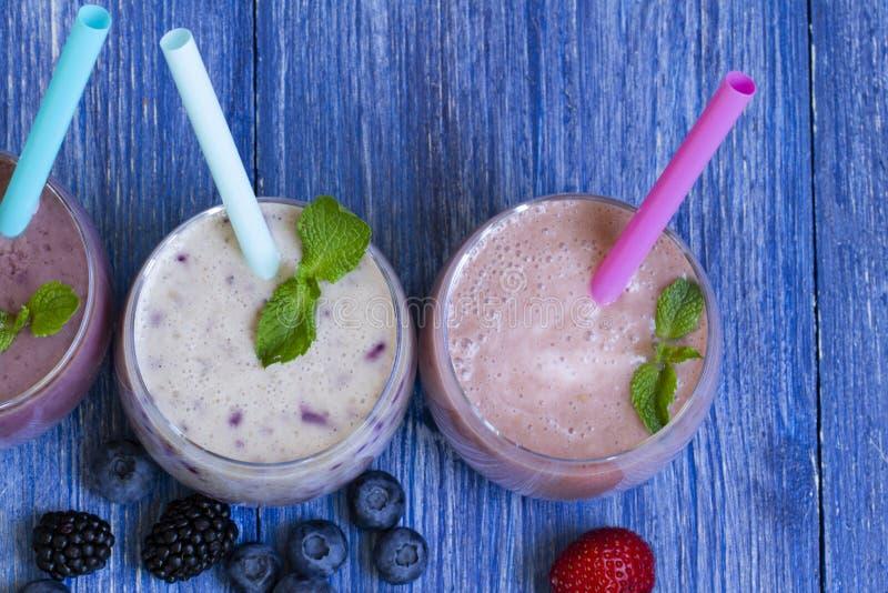 Hallon jordgubbe, blåbärsmoothie på blå träbakgrund Milkshake med nya bär fruktsmoothie med arkivfoton