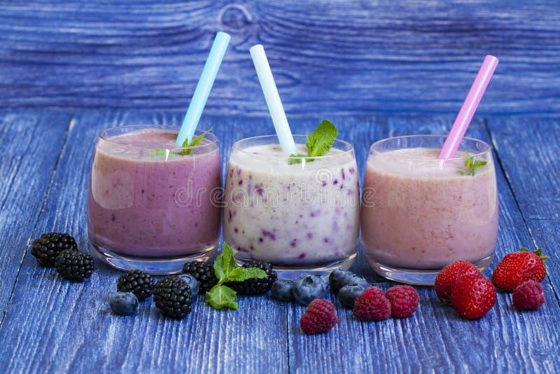 Hallon-, jordgubbe- och blåbärsmoothie på blå träbakgrund Milkshake med nya bär bäryoghurt med arkivfoton