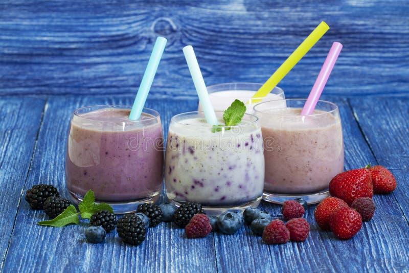 Hallon-, jordgubbe- och blåbärsmoothie på blå träbakgrund Milkshake med nya bär bäryoghurt med royaltyfri bild