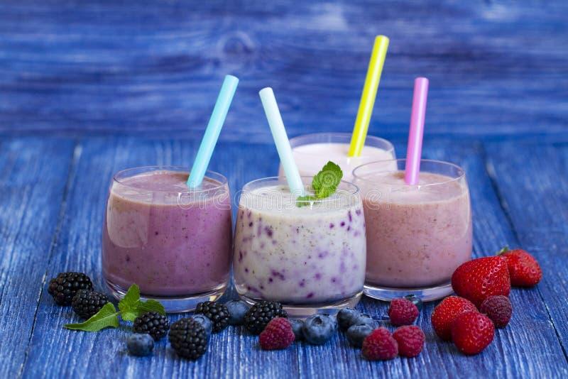 Hallon-, jordgubbe- och blåbärsmoothie på blå träbakgrund Milkshake med nya bär bäryoghurt med fotografering för bildbyråer