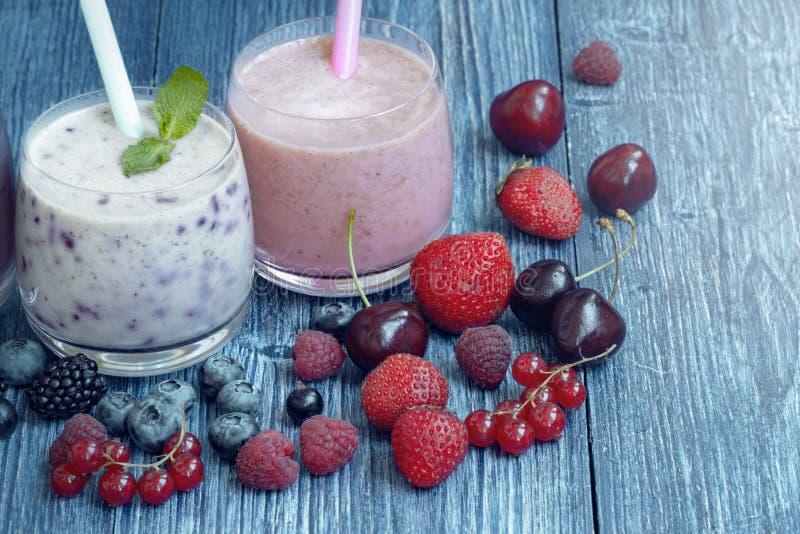 Hallon-, jordgubbe- och bl?b?rsmoothie p? bl? tr?bakgrund Milkshake med nya b?r b?ryoghurt med fotografering för bildbyråer