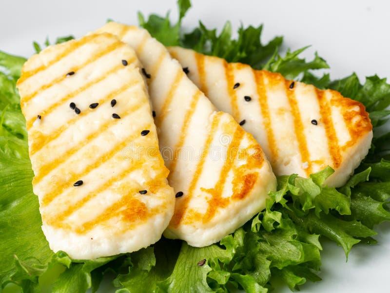 Halloumi grigliato, macro formaggio fritto con l'insalata della lattuga Dieta equilibrata, piatto bianco, vista laterale fotografia stock libera da diritti