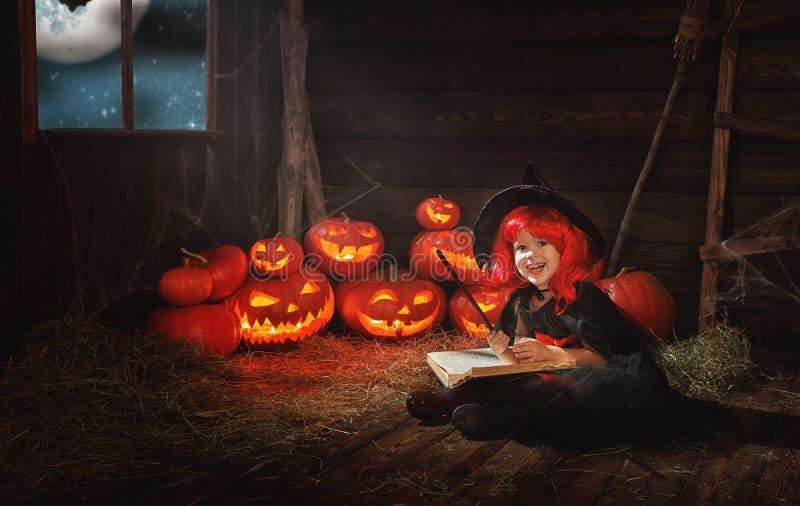halloween ведьма ребенка маленькая с тыквой Джеком и волшебным bo стоковые изображения