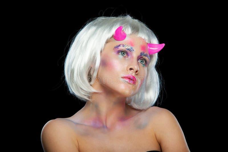 halloween Портрет молодой красивой девушки с составом С белыми волосами и розовыми рожками дьявола Изолировано на черноте стоковое изображение