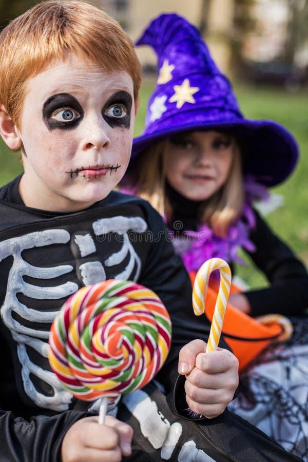 halloween Скелет и ведьма держа красочные конфеты стоковые изображения rf