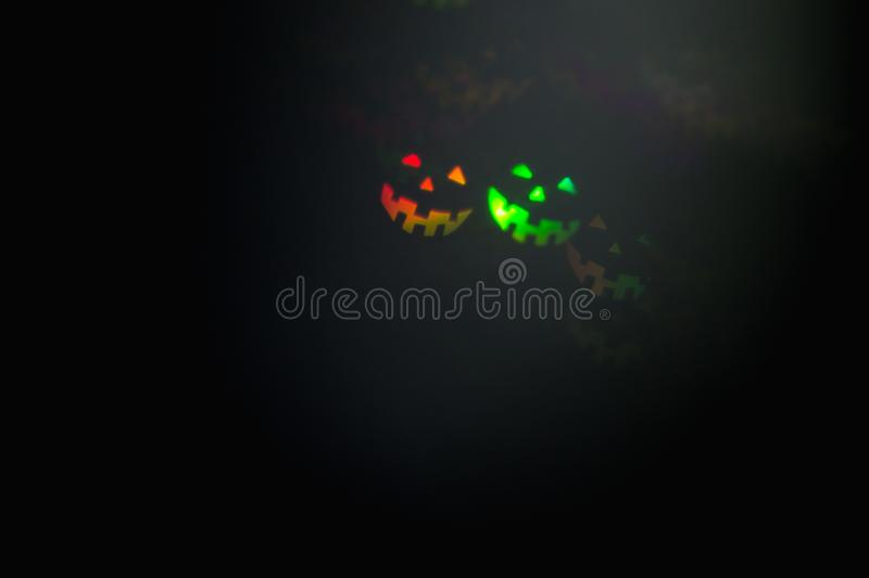 Halloween abstract glowing blurred background. Close up bokeh in shape of Halloween emoticons . Defocused blinking shaped lights. stock image