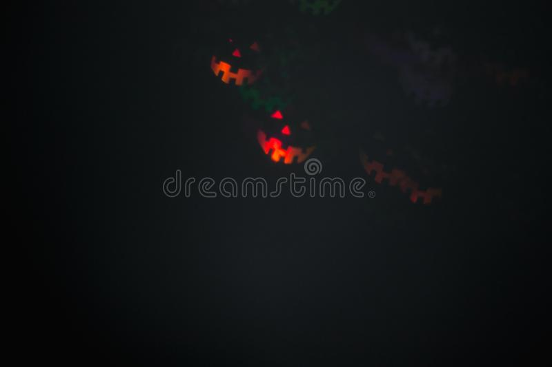 Halloween abstract glowing blurred background. Close up bokeh in shape of Halloween emoticons . Defocused blinking shaped lights. Background for halloween stock images